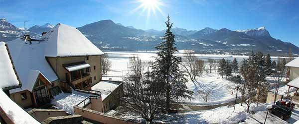 Village le Chadenas en hiver avec la neige et vue sur le lac de Serre-Ponçon