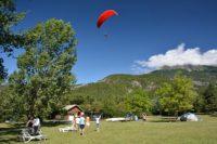 Parapente au dessus du village Le Chadenas au bord du lac de Serre-Ponçon