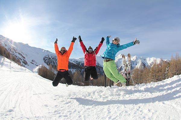 Saut des skieurs heureux en séjour à la montagne