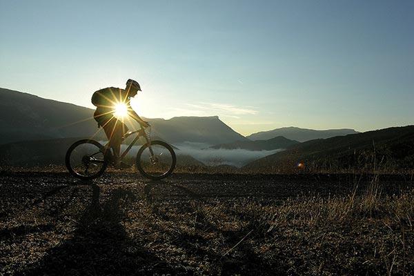 Cycliste au coucher de soleil à la montagne